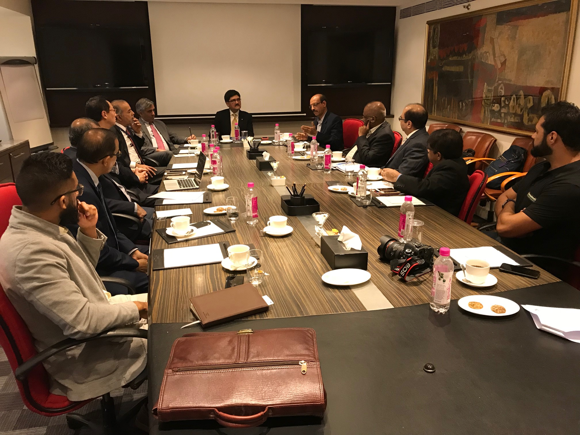 Photo of representatives from IC-IMPACTS, UBC, SenseIndia Ltd, Starmass Environment Technologies, Infrastructure Leasing and Financial Services (IL&FS), the National Academy of Construction (NAC), Tata Consultancy Services (TCS), and T-Hub around a table for a signing ceremony at Taj Tower, Business Center.