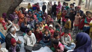 Tika Vaani Project, photo of dozens of seated people at a community meeting in India